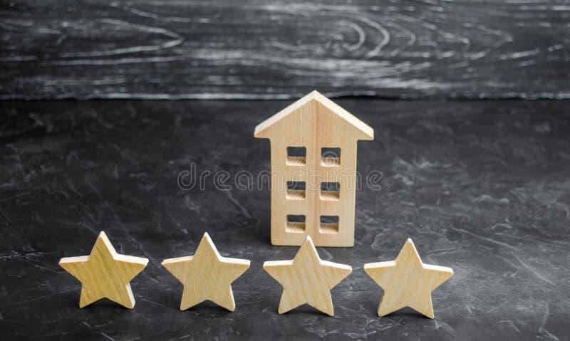 Trähus och fyra stjärnor på en grå bakgrund Värdering av hus och den privata egenskapen Köpa och sälja som hyr lägenheter arkivfoton