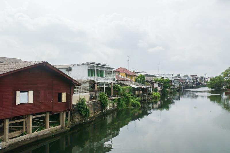 Trähus och modern byggnad på flodstranden i Thailand arkivbilder