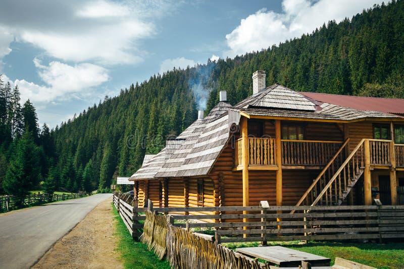 Trähus som nära omges av berg och den gröna barrskogen till bygdvägen, sommartid royaltyfri fotografi