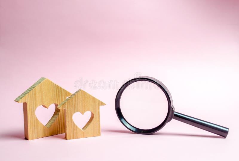 Trähus två med en hjärta och ett förstoringsglas Begreppet av att finna som man har råd med hus för unga familjer och gift arkivbild