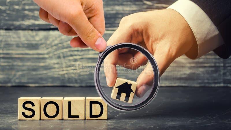 Trähuset med inskriften sålde försäljning av egenskapen, hem som man har råd med hus Sale av lägenheter fastighetsmäklareservice arkivfoton