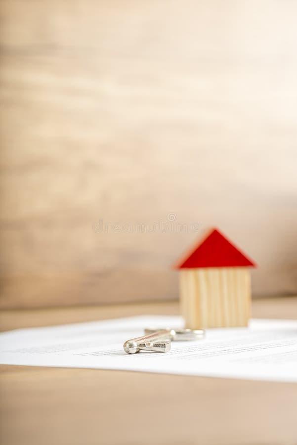 Trähusminiatyr och hustangent som ligger på avtal royaltyfri foto