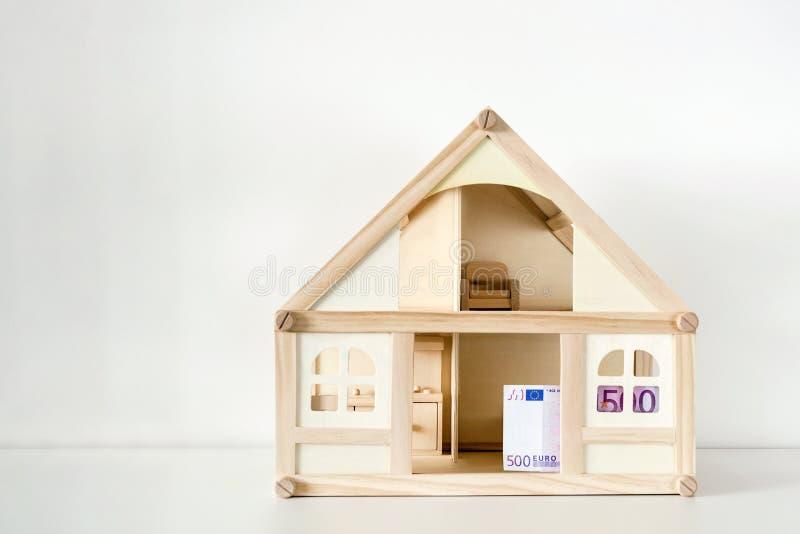 Trähusmodell med räkningen för euro 500 Hushyra och försäljning Kostnader och kostnader för husatt behandla Husbesparingbegrepp C royaltyfri bild