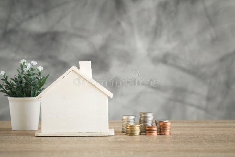 Trähusmodell och myntpengar på den wood tabellen för finans och arkivbild