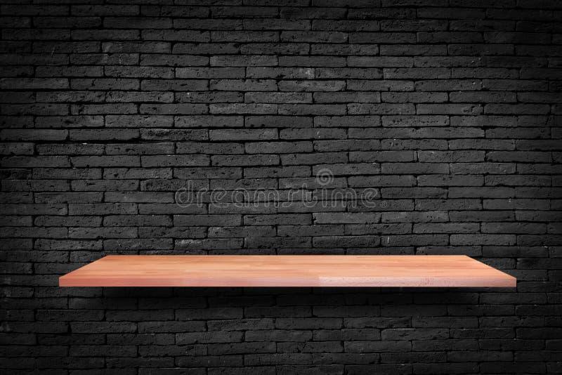 Trähyllan på svart bakgrund för tegelstenvägg - kan användas för royaltyfri bild