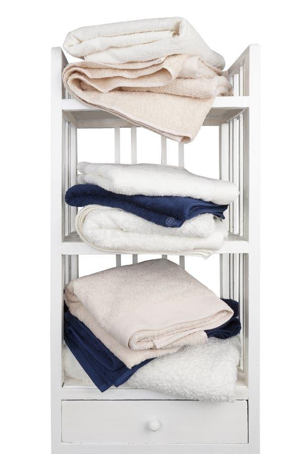 Trähyllor med handdukar som isoleras på vit bakgrund royaltyfri foto