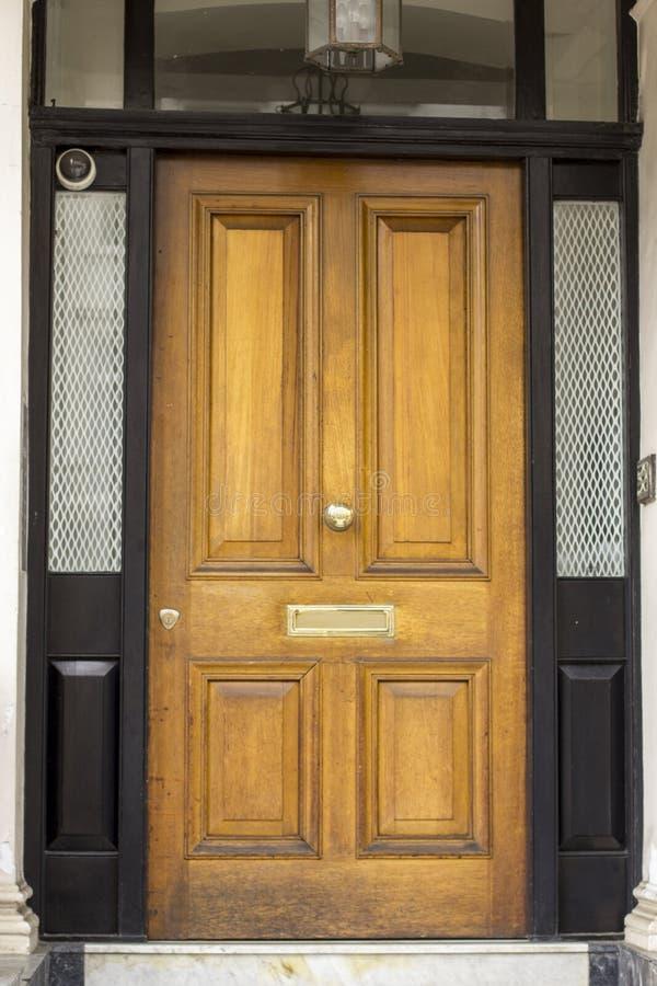 Träingångsdörr till bostads- byggnad i London Typisk dörr i den engelska stilen arkivfoton
