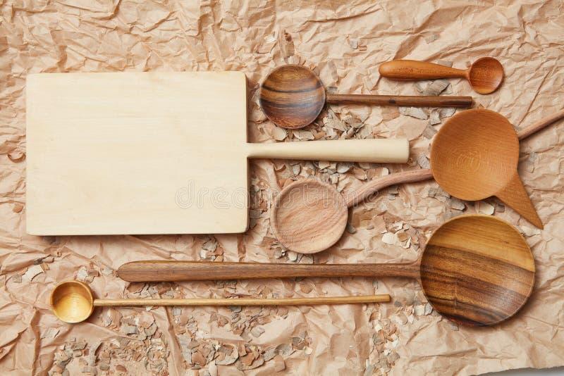 Träkökredskap på bakningpapper royaltyfria foton