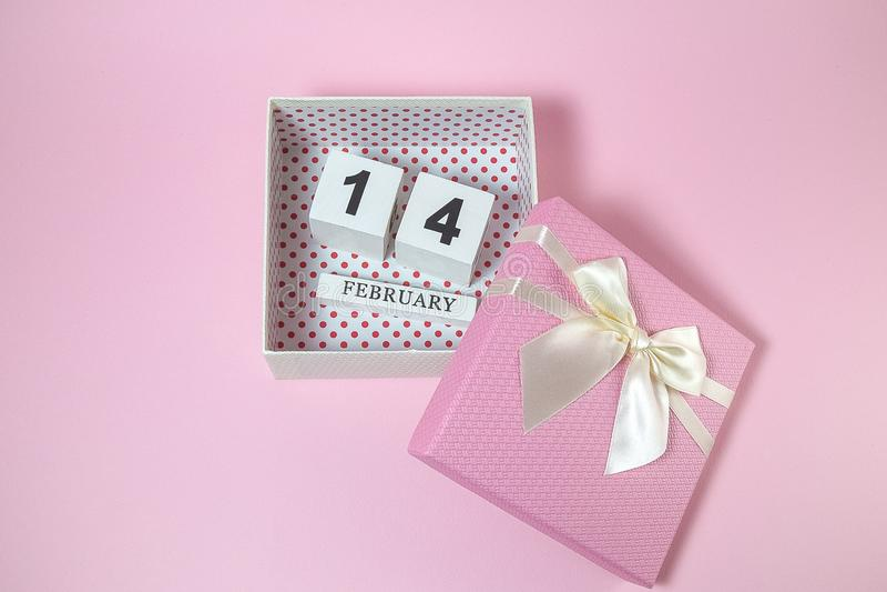 Träkalender i den rosa gåvaasken på den rosa bakgrunden arkivbilder