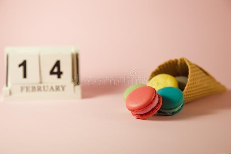Träkalender med färgrika macarons i glasskotte på den rosa bakgrunden arkivbild