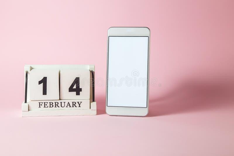 Träkalender och smartphone med den tomma skärmen på den rosa bakgrunden royaltyfri bild