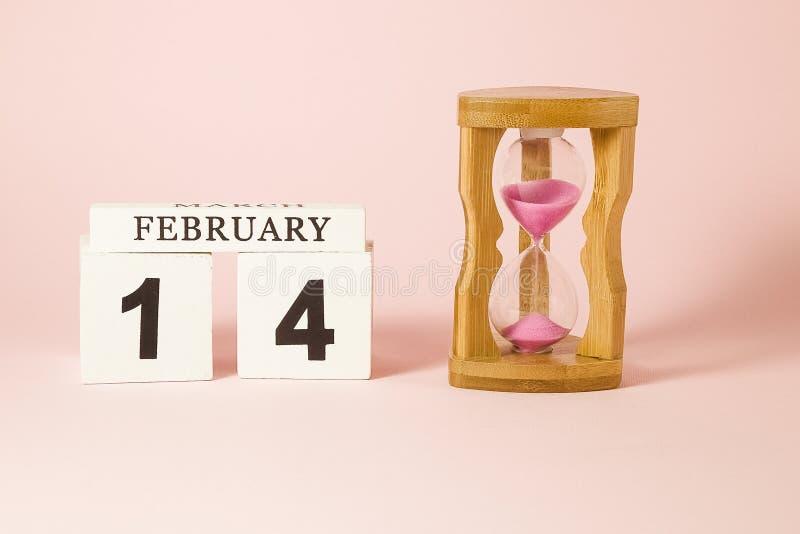Träkalender- och timglasklockan påminner dig av tid arkivfoto
