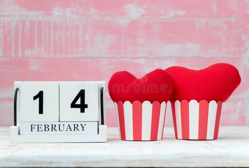 Träkalendern på Februari 14, två röda hjärtor var den förlade sidan - vid - sidan, och bakgrunden är rosa vektor för valentin för royaltyfria bilder