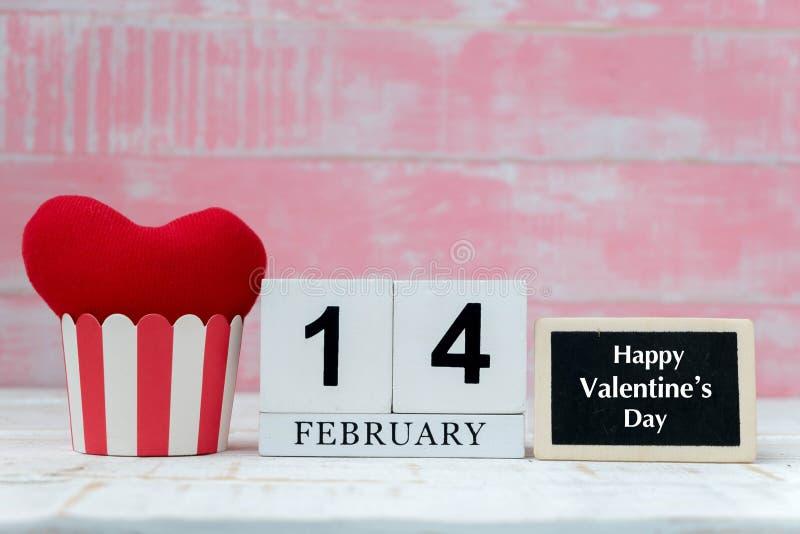 Träkalendern på Februari 14, två röda hjärtor var den förlade sidan - vid - sidan, och bakgrunden är rosa vektor för valentin för arkivfoto