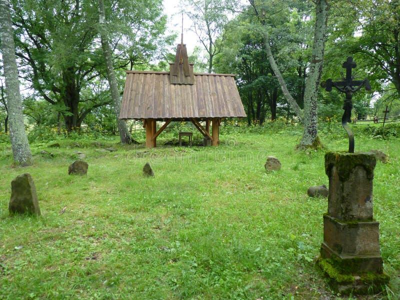 Träkapell på den gamla kyrkogården som omges av härliga gamla gravstenar och kors royaltyfri bild