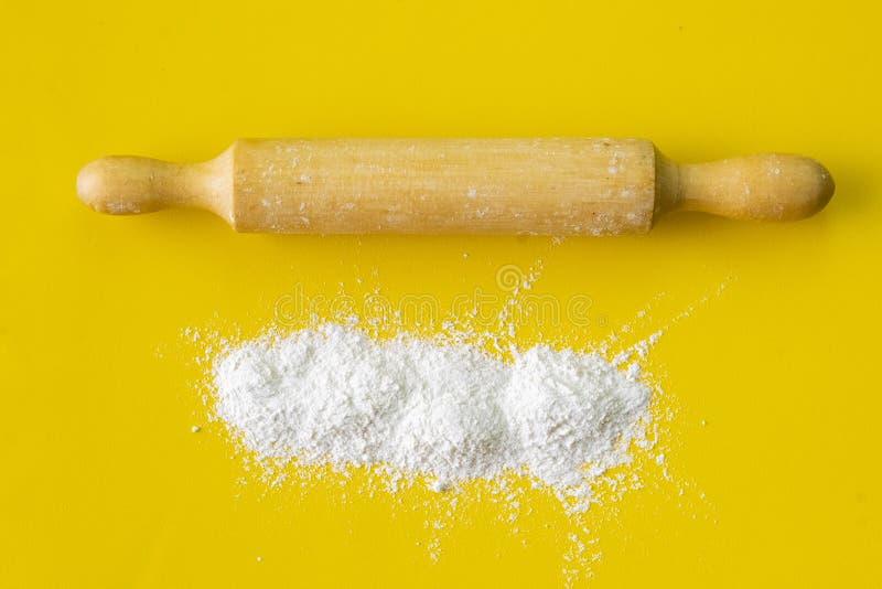 Träkavel och vitt vetemjöl på tabellen, utrustningen och ingredienserna för matlagningar royaltyfria bilder