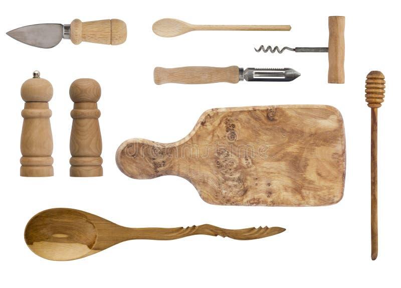 Träkitchenware som isoleras på vit bakgrund Skedar korkskruvet, knivar, bräde, saltar shaker och peppar royaltyfria bilder
