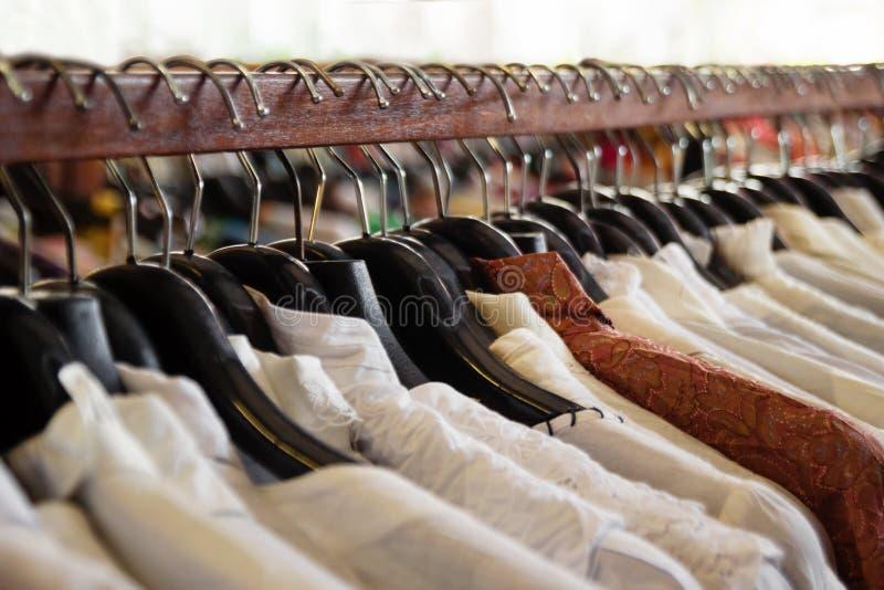 Träkläderkuggar med hängare och med vit- och bruntskjortor arkivbild