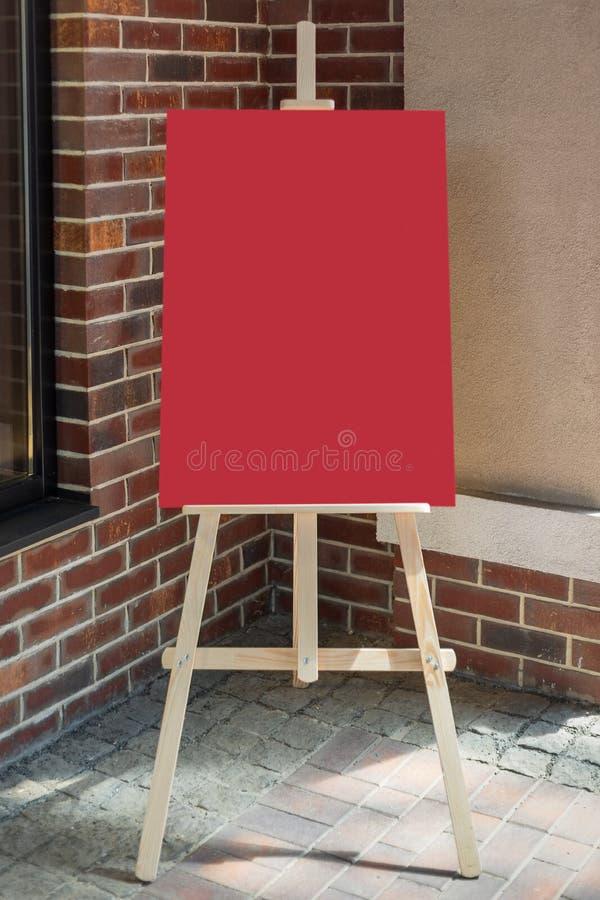 Träkonstnär Easel med den röda tomma modellaffischen för din design fotografering för bildbyråer