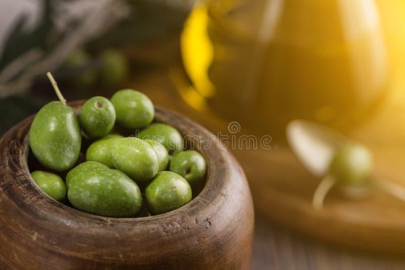 Träkopp av oliv med extra jungfrulig olivolja i glasflaska på lantlig bakgrund close upp royaltyfri bild