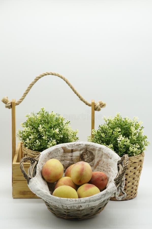 Träkorg med persikor på vit bakgrund arkivbild