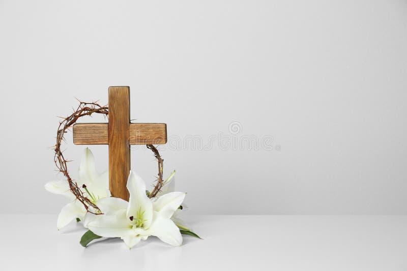 Träkors, krona av taggar och blomningliljor på tabellen mot ljus bakgrund arkivbild