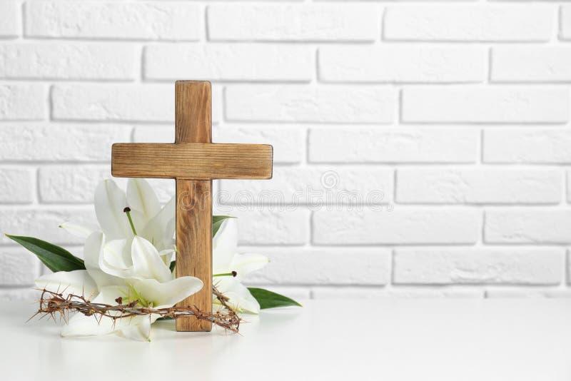 Träkors, krona av taggar och blomningliljor på tabellen mot tegelstenväggen fotografering för bildbyråer