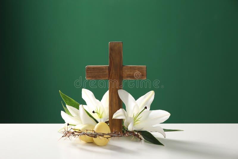 Träkors, krona av taggar, påskägg och blomningliljor på tabellen arkivbild
