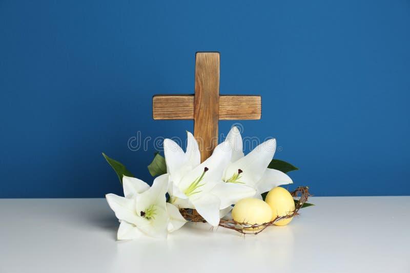 Träkors, krona av taggar, påskägg och blomningliljor på tabellen arkivfoton