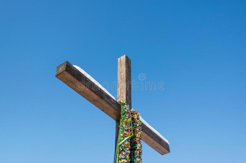 Träkristenkors med gröna gula band för krans och för blått på den vanliga bakgrunden för blå himmel, begrepp av hopp royaltyfri fotografi