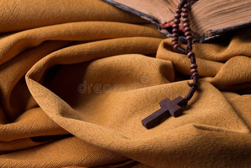Träkristenkors och radband och gammal bibel på guld- tyggardin Helgedomen bokar royaltyfri bild