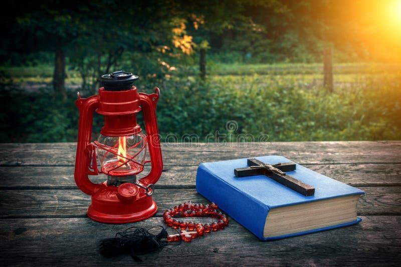 Träkristenkors på bibeln, den brinnande fotogenlampan och bönpärlor på den gamla tabellen Räddning av anda och sonande av synder royaltyfri foto