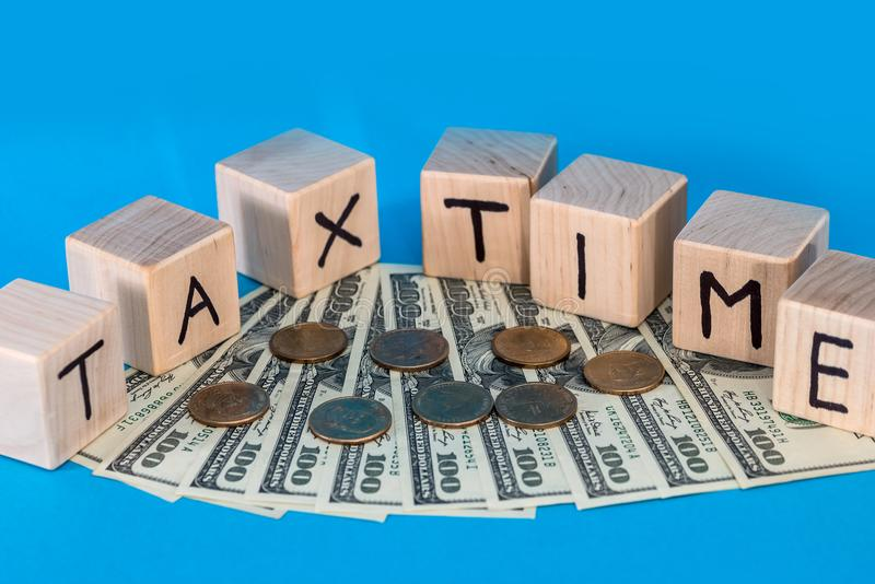 Träkub med myntet för nad för för texskatttid och dollar på blått royaltyfri bild
