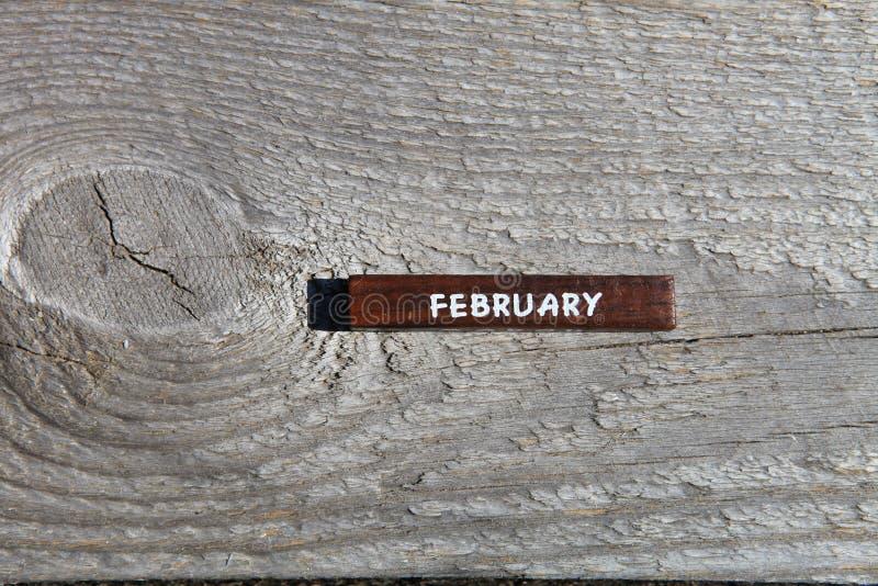 Träkub med namnet av månaden på det gamla brädet Februar royaltyfria bilder