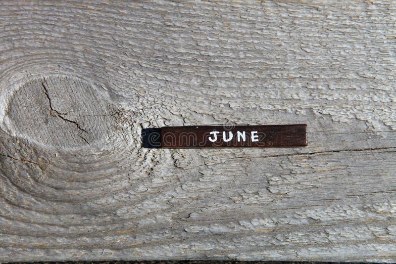 Träkub med namnet av månaden på det gamla brädet juni royaltyfria foton