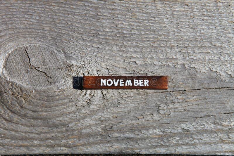 Träkub med namnet av månaden på det gamla brädet Novembe arkivfoton