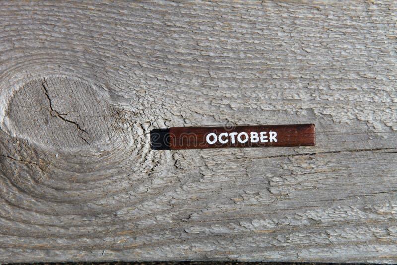 Träkub med namnet av månaden på det gamla brädet oktober royaltyfria bilder