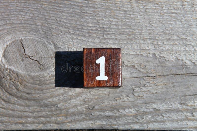 Träkub med numret ett arkivfoto