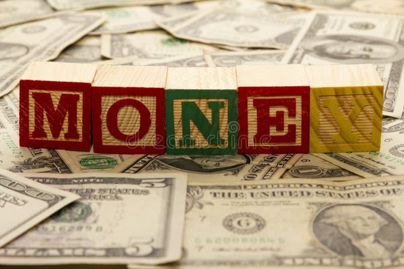 Träkuber med ordpengarna på dollar arkivbilder