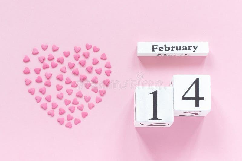Träkubkalender Februari 14th och hjärta från rosa konfektstänk i en hjärtaform på pastellfärgad rosa bakgrund royaltyfri fotografi