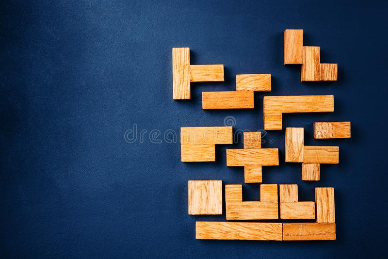 Träkvarter för olika geometriska former på en mörk bakgrund Idérikt logiskt tänka och begrepp för problemlösning kopiera avstånd royaltyfri fotografi