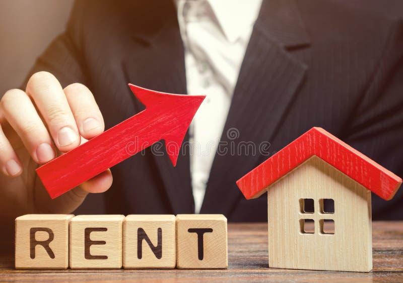 Träkvarter med hyran, huset och upp pilen för ord Begreppet av den höga kostnaden av hyra för en lägenhet eller ett hem intresse royaltyfri foto