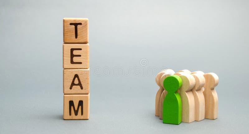 Träkvarter med ordlaget och en folkmassa av arbetare med en ledare Begreppet av ett starkt pålitligt affärslag Teamwork royaltyfri fotografi