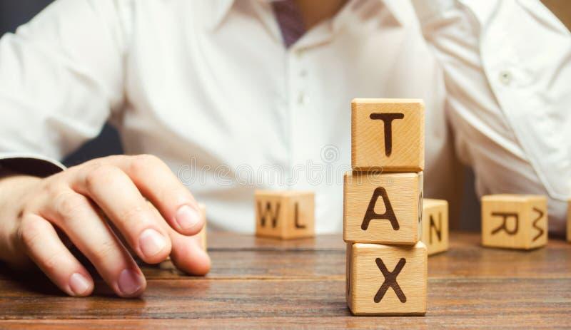 Träkvarter med ordskatten och en affärsman som sitter på tabellen Framställning av det högra beslutet pay beskattar tid till mot  royaltyfri foto