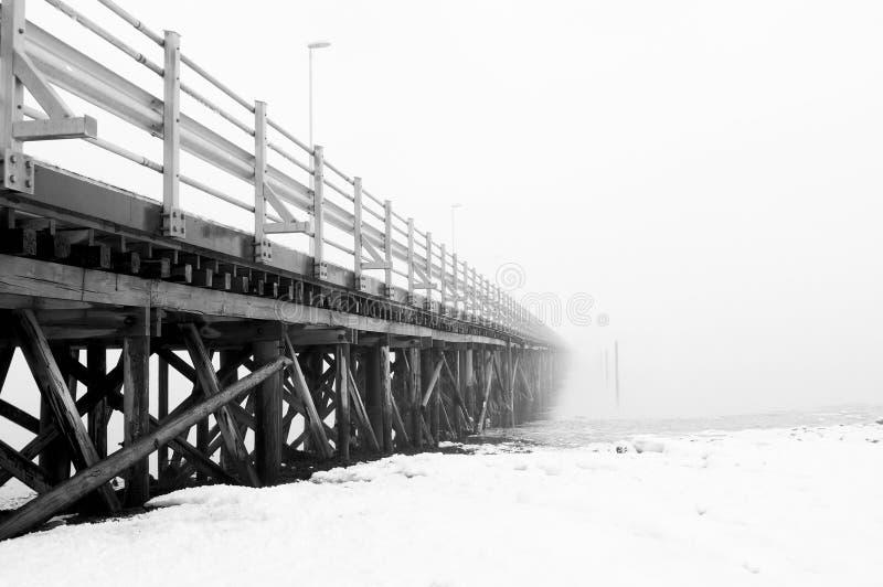 Träläskig bro som försvinner i dimman Bro som leder till ingenstans arkivfoto