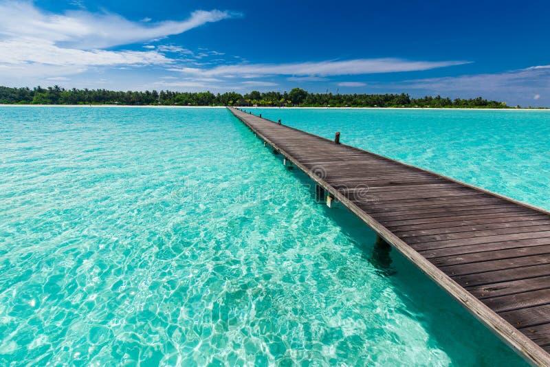 Trälång brygga över lagun i Maldiverna med fantastiskt vatten royaltyfri fotografi