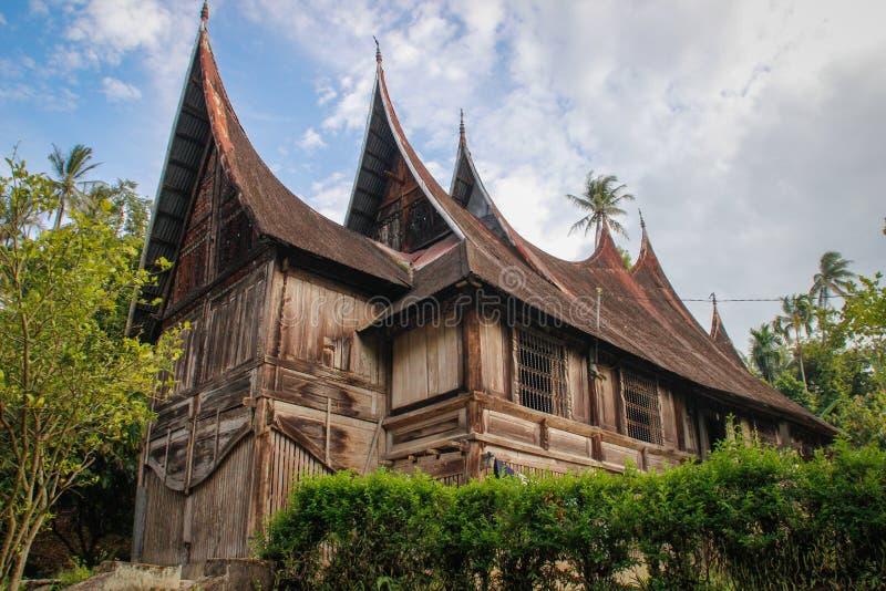 Trälantligt hus med ett ovanligt tak i byn av det Minangkabau folket på ön av Sumatra royaltyfria foton