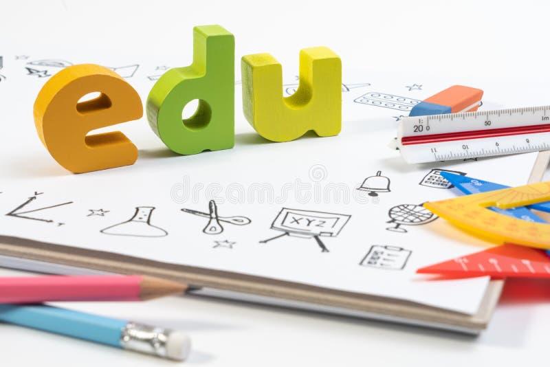 Träleksak EDU på anteckningsboken med teckningsklottret för utbildning arkivfoto