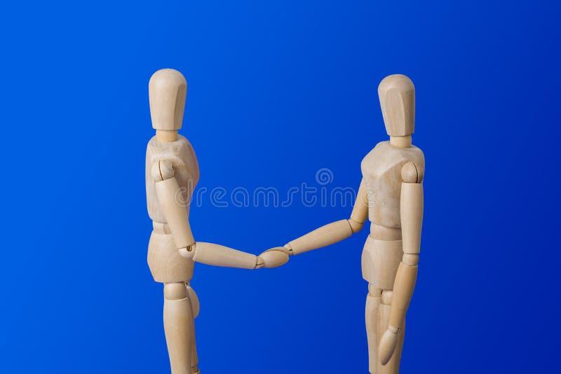Träleksakdiagram handskakning på blått royaltyfria foton