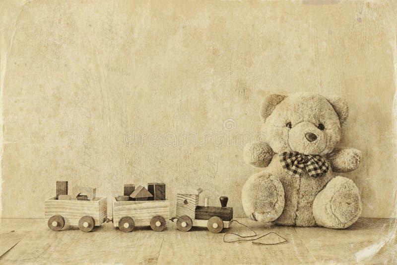 Träleksakdrev och nallebjörn över trägolv Svartvitt stilfoto arkivfoton